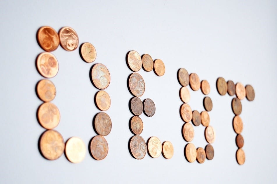 Coins forming the word debt