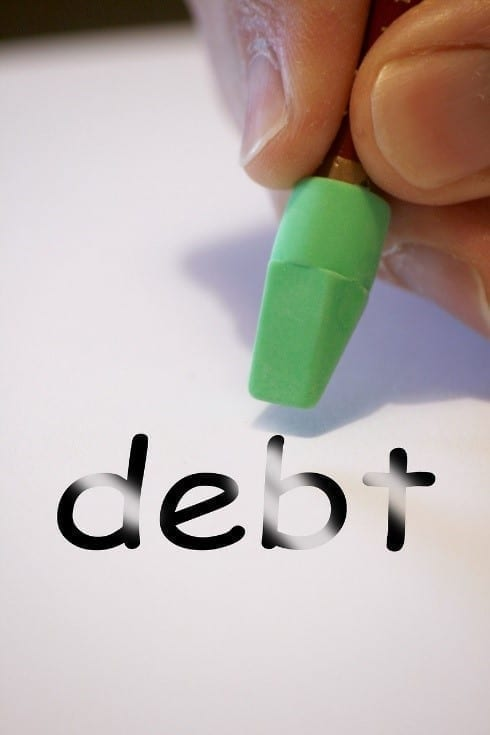 Hand writing the word debt using a green pen