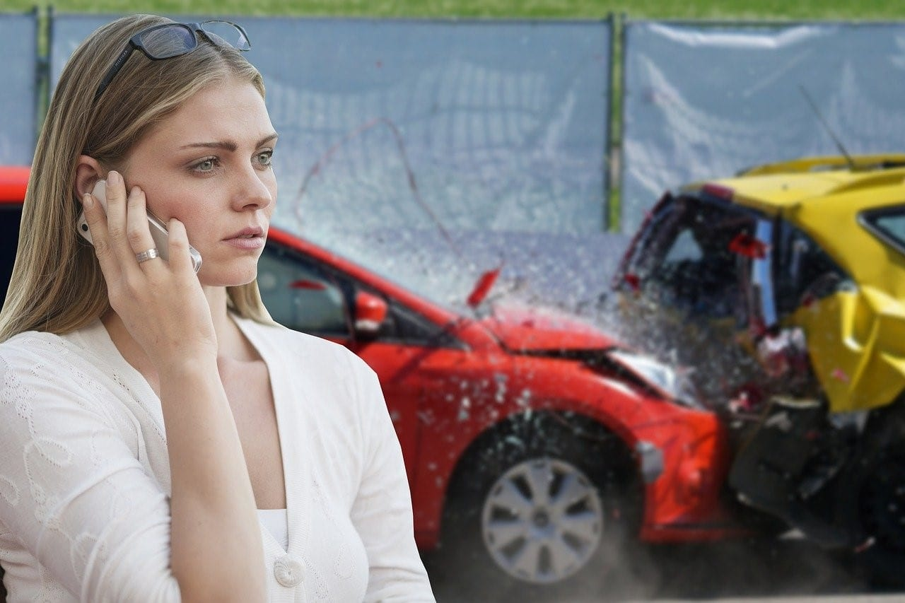 Woman involved in a car collision using her phone to call for assistance
