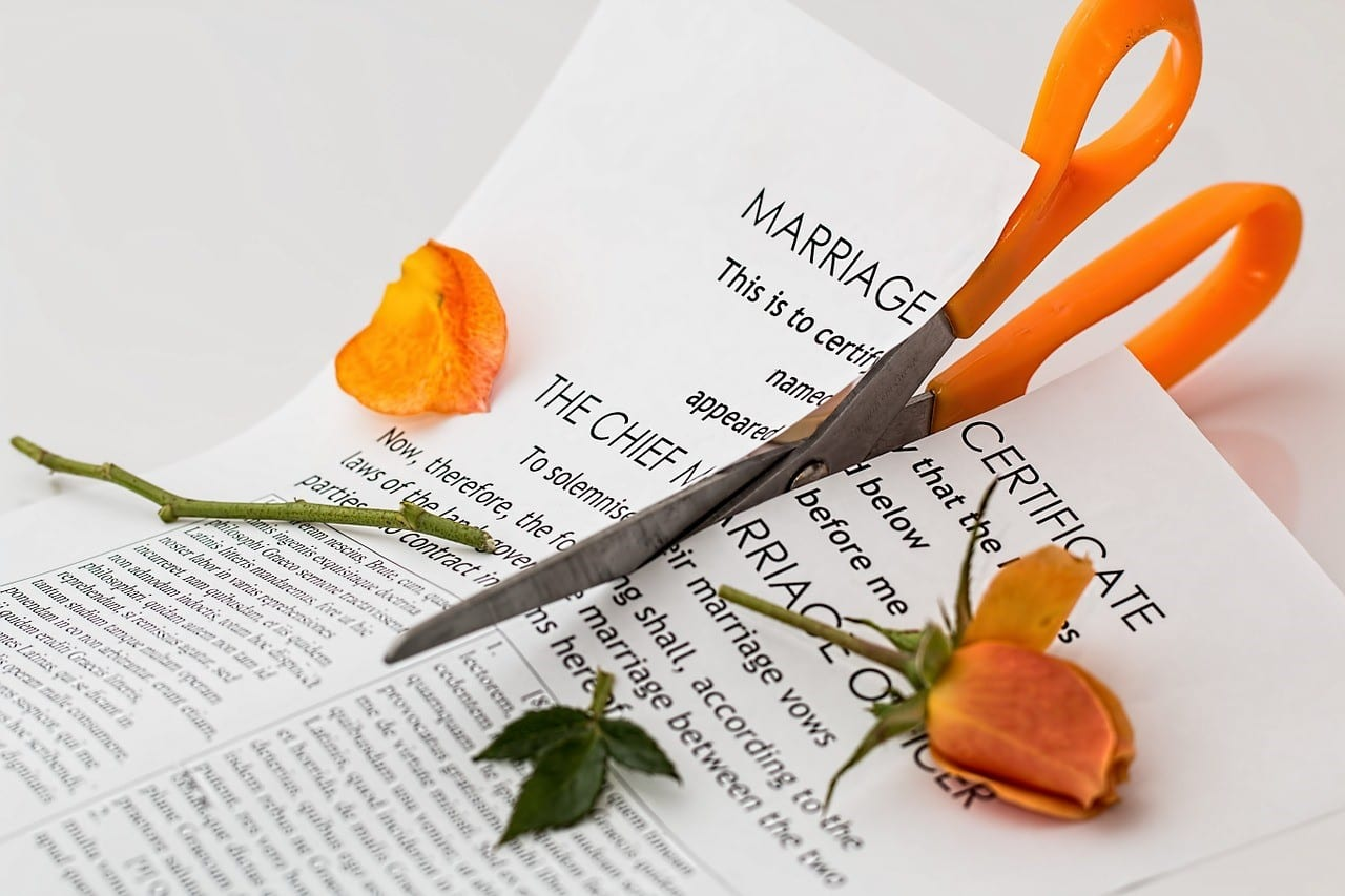 Marriage certificate being cut with scissors