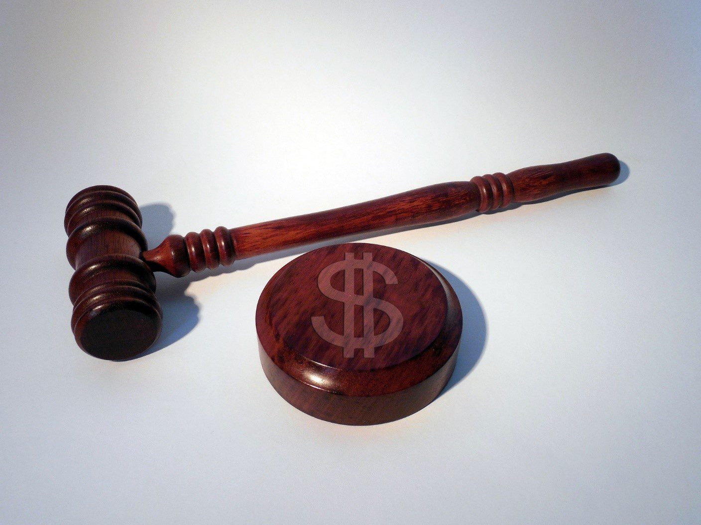 A wooden gavel and block with dollar sign