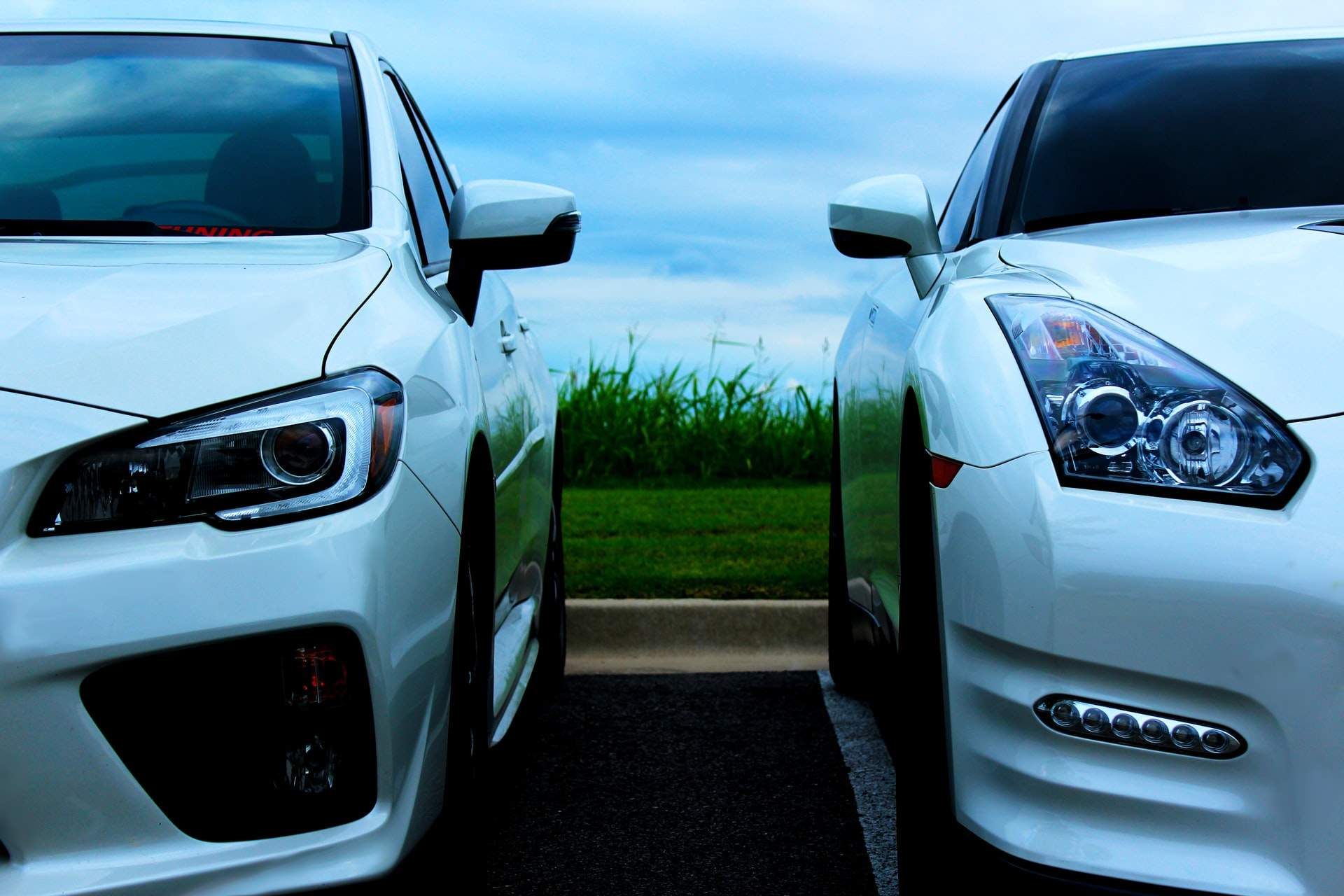 Two white cars parked next to each other