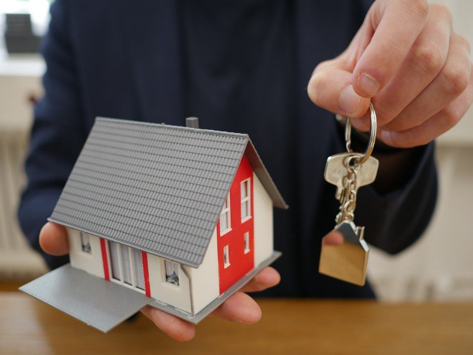 Person holding a small model house and a key
