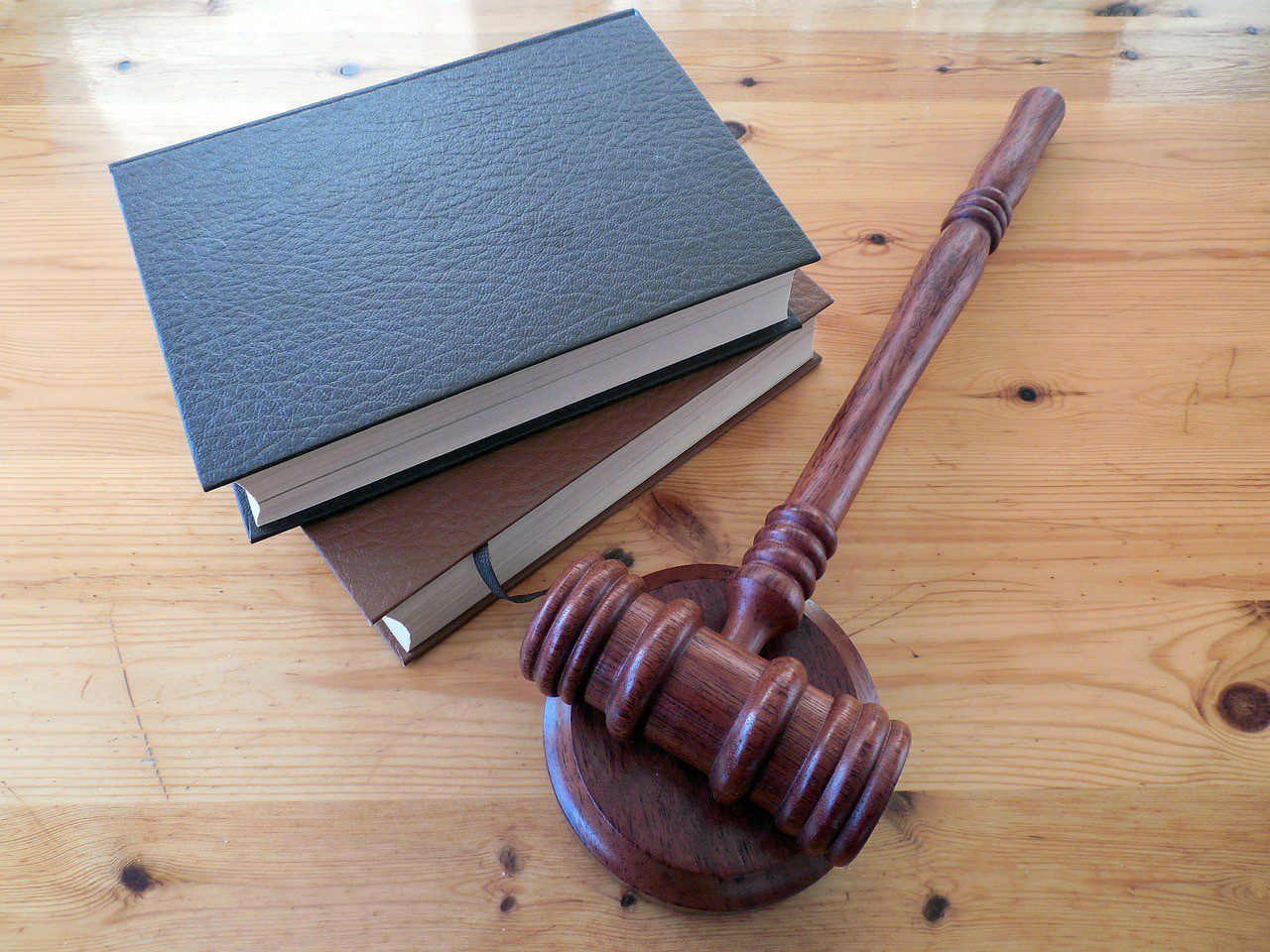 Two books and a gavel on a wooden table
